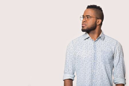 Pensive african American man in glasses isolated on grey studio background think look at blank copy space aside, thoughtful black male wear spectacles pondering about good sale deal or offer