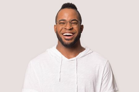 Excited african American young man in glasses and sport clothes isolated on grey background laugh looking ta camera, smiling black millennial male in casual wear and spectacles feel happy overjoyed Zdjęcie Seryjne