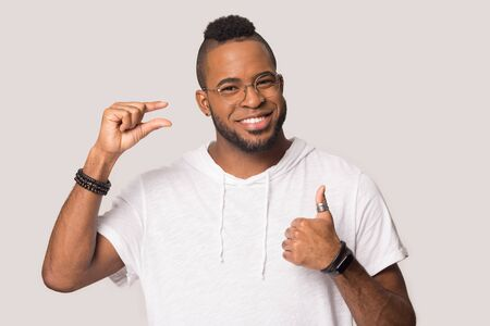Smiling african American man isolated on grey studio background show thumb up gesture talk about small prices, happy black male look at camera recommend service, express little by finger