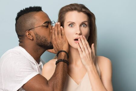 Millennial african American man in glasses tell secret to surprised stunned Caucasian woman, two multiracial people isolated on blue studio background share shocking unexpected news, promotion offer