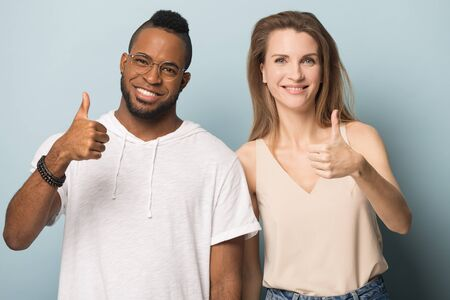 Happy african American man and Caucasian woman isolated on blue studio background show thumb up, smiling multiethnic couple or young people feel satisfied recommend service or brand
