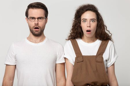 Unpleasantly surprised millennial couple looking at camera, isolated on grey white studio background. Shocked young man and stunned curly girl hear unbelievable awful news, negative emotions concept.