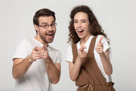 Joyful happy young family couple looking and pointing fingers at camera, isolated on grey white studio background. Cheerful young man and millennial woman appealing to you, good choice concept.