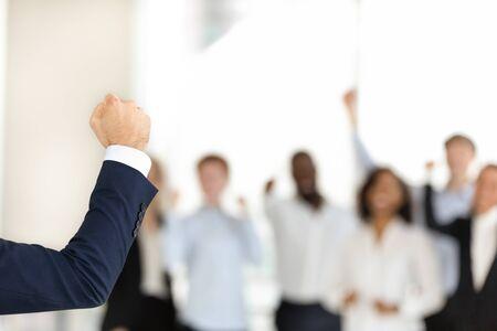 Erfolgreicher selbstbewusster Geschäftsmann lässt die geballte Faust der Rede zeigen, demonstriert Kraft und Stärke, aufgeregte Geschäftsleute des vielfältigen Arbeitsteams unterstützen den männlichen Führer zusammen. Einheit, Führungskonzept