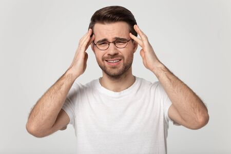 Tired millennial man in eyewear massaging temples, suffering from sudden headache head shot close up portrait. Young stressed unhealthy guy feeling strong throbbing pain, isolated on grey background.