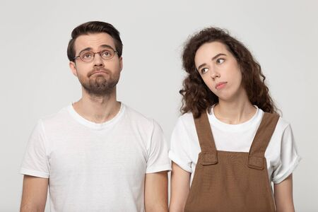 Upset not concentrated exhausted millennial couple feeling bored, lack of motivation or interest, looking away, isolated on grey white studio background. Sad young friends need weekend rest. Stockfoto