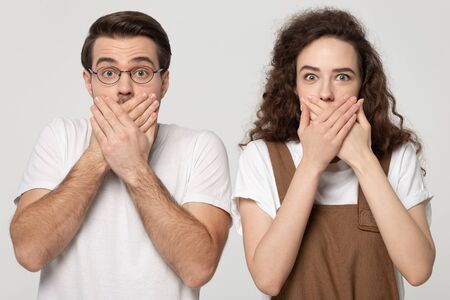 Surprised shocked millennial couple covering mouths with hands, looking at camera, isolated on grey white studio background portrait. Young man and curly woman expressing unexpectedness, fear or awe.