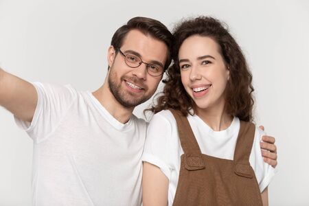 Happy millennial loving smiling couple taking selfie shot, isolated on grey white studio background. Young guy with girlfriend making photo for social networks while dating, relationship concept. Zdjęcie Seryjne