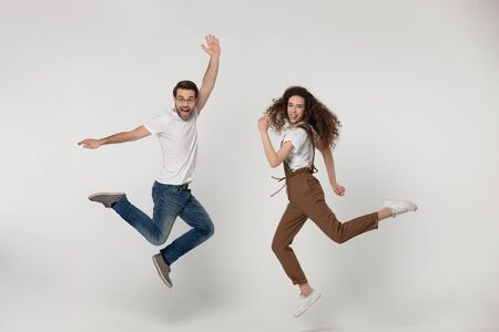 Joyful young man and happy millennial girl jumping high with raised hands and bent in knees legs, flying, having fun during photo shooting process near softbox light, isolated grey background. Stock fotó - 138462825
