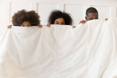 African little daughter mother and father looks at camera standing hiding behind white blanket holding duvet. Home laundry service, advertisement for quality bedclothes store, have fun indoors concept Banco de Imagens