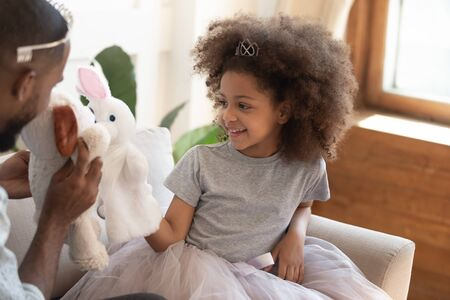 Little african daughter play with father people sit on couch holding soft animals toys acting out fun performance, good pastime for small children stimulates imagination encouraging creativity concept