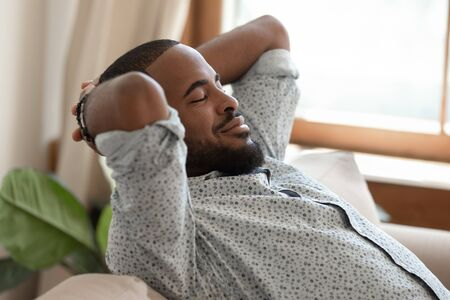 Close up side view african guy closed eyes put hands behind head resting leaned on sofa thinking feels satisfied, recalls pleasant moments of past day do meditation reducing fatigue and stress concept