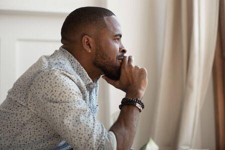 Nahaufnahme Seitenansicht afrikanischer ernster Kerl berührt das Kinn Denken fühlt sich besorgt wegschauen allein drinnen sitzen, Tagträumen und nostalgische Stimmung, Suchproblemlösung machen wichtiges Entscheidungskonzept