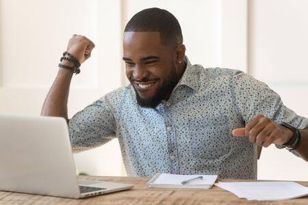 Afrikanischer emotionaler Kerl, der am Schreibtisch sitzt, schaut auf den Bildschirm des Notebooks, liest die Nachricht, fühlt sich aufgeregt, die Faust heben macht Ja, ich habe es getan Geste, Studenten, Universitätszulassung, Arbeitslose, Job, Lotteriegewinner-Konzept