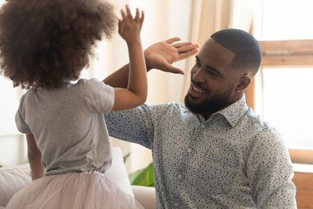 American family spend time at home having fun focus on african father raise hand gives high five to daughter symbol of support and unity, different generations warm relations and understanding concept