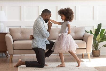 In cozy living room african dad got down on one knee kisses hand of daughter princess wearing fluffy pink skirt, chivalrous gesture, courtesy and politeness, devotion admiration, good manners concept Stock Photo