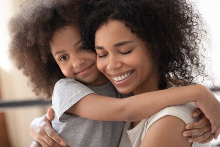 Close up beautiful faces happy family portrait loving african daughter hugs mother, mom enjoy moment of tenderness closed eyes feels deep love to her pretty kid, adoption protection offspring concept Stock Photo
