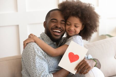 African daddy on Father Day received from caring little daughter paper postcard written message best wishes, drawn red heart as symbol of love and deep affection, family holidays celebration concept Banco de Imagens