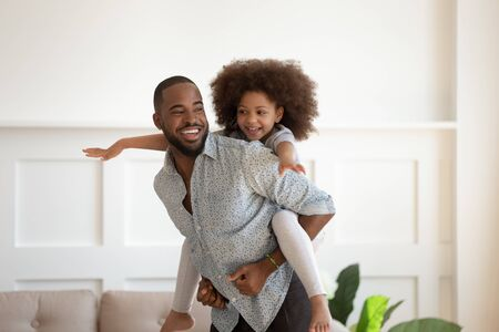Handsome african father piggybacking little daughter playing at modern light living room, daddy holding riding on back adorable cheerful kid girl enjoy active game pastime free time together concept