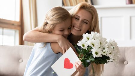 Joyful adorable blonde little preschool daughter congratulating smiling mother with birthday or special occasion, presenting flowers and handmade card. Thankful young mommy cuddling child girl.