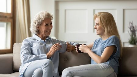 Happy older retired woman mother chatting with pleasant smiling grown up daughter, sitting together on cozy sofa, drinking tea coffee. Loving two generations family enjoying free leisure time at home. 版權商用圖片