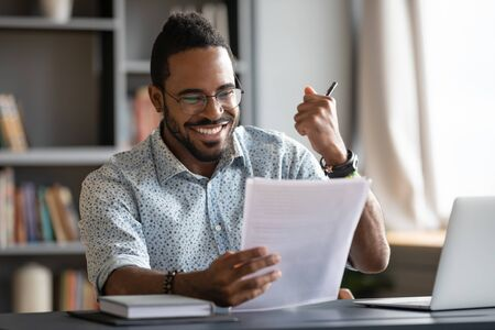 Happy satisfied young african male professional winner overjoyed hold reading good news in document get new job concept receive salary rise payment taxes refund loan approval message sit at work desk Stock Photo