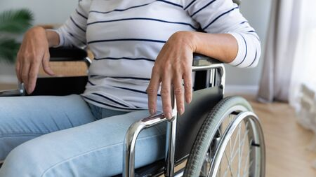 Close up disabled older woman sitting in wheelchair with arms on armrests, resting at home, rehabilitation after injury, mature female patient in nursing house, disability and handicap, healthcare