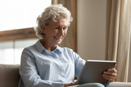 Happy older woman holding digital tablet, reading electronic book alone at home. Smiling middle aged user web surfing, searching information, shopping online in internet store, chatting with friends.