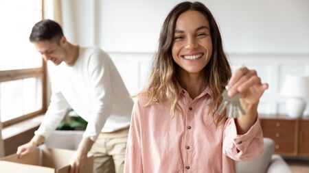Smiling millennial Caucasian girl look at camera hold showing house keys excited to move together with husband, portrait of overjoyed young wife relocating with spouse, couple apartment rent