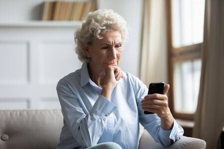 Thoughtful middle aged hoary woman sitting on couch, holding smartphone in hands, reading news. Pensive older woman worrying about bank loan debt sms notification, thinking of financial problems.
