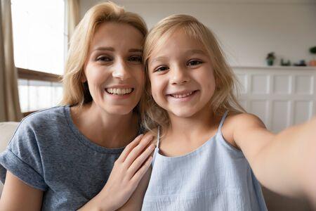 Web cam visualizza adorabile bambina in età prescolare che fa selfie con una giovane madre attraente a casa. Sorridente donna bionda in posa per il minerale di foto che registra video divertenti e carini con la figlia di un bambino piccolo al chiuso.