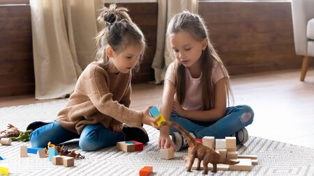 Small girls sisters sit on warm wooden floor in living room play with building bricks together, little cute caucasian kids cousins have fun engaged in children activity game with toys at home