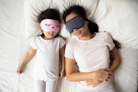 Blick von oben auf die ruhige asiatische Mutter und Tochter in Schlafmaske, entspannen Sie sich in einem bequemen weißen Bett zusammen, die vietnamesische junge Mutter und das süße kleine Mädchen ruhen sich aus und machen im gemütlichen Schlafzimmer ein Nickerchen Standard-Bild