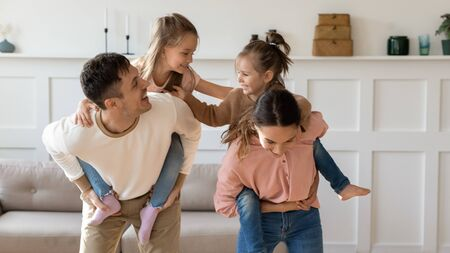 Little preschooler girls children piggyback young parents play together in living room at home, loving mom and dad carry on backs small daughters have fun engaged in funny activity at family weekend