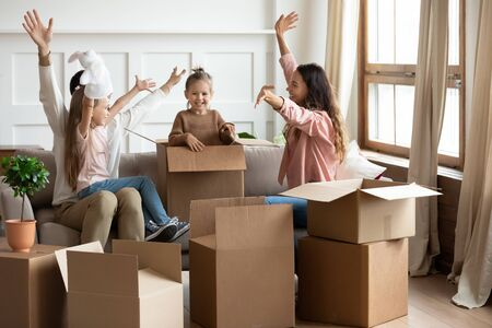 Overjoyed young family with little daughters jump out of cardboard boxes play together in living room on moving day, happy parents have fun with small girl kids excited relocating to new house