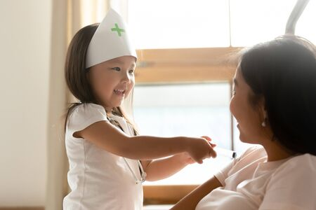 Cute small Asian girl as doctor play with young ethnic mom give injection to patient, little Vietnamese child act like nurse engaged in funny game with mother or nanny at home, future career concept