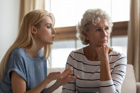 Irritated young woman asserting opinion to offended middle aged mother at home. Annoyed blonde grown up daughter arguing with stubborn mature elderly mom, two generations family disagreements concept. Stock Photo