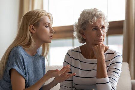 Mujer joven irritada afirmando su opinión a la madre de mediana edad ofendida en casa. Hija adulta rubia molesta discutiendo con terca madre anciana madura, concepto de desacuerdos familiares de dos generaciones. Foto de archivo