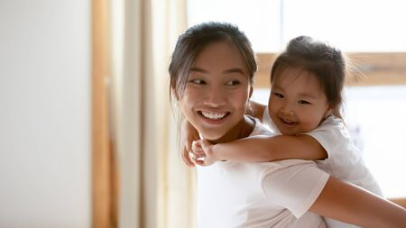 Cute little Vietnamese girl piggyback overjoyed ethnic young mother having fun at home, small smiling Asian daughter child play with happy biracial millennial mom or nanny, entertainment concept Banco de Imagens
