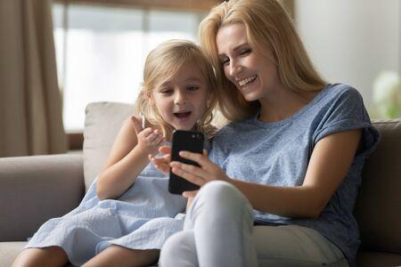 Śliczna mała dziewczynka w wieku przedszkolnym zachwycona zabawną grą mobilną, spędzającą czas razem z blond matką. Uśmiechnięta atrakcyjna młoda kobieta pokazująca ciekawe aplikacje ciekawskiej małej córeczce.