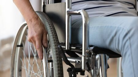 Close up disabled older woman sitting in wheelchair, touching wheels, moving at home alone, rehabilitation and recovery after injury, medical equipment, disability and healthcare Zdjęcie Seryjne - 138652651
