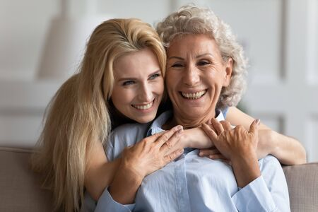 Attractive smiling young blonde woman embracing from back sitting on couch older pleasant mommy. Loving two female generations family showing support care, enjoy tender sweet moment at home.