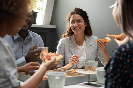 Happy diverse millennial colleagues chat laughing drinking coffee eating pizza during office lunch, smiling excited multiracial employees have fun enjoy tasty Italian fast food from takeaway delivery