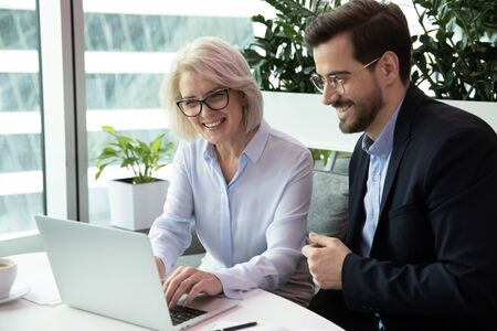 Happy middle aged female team leader working on computer with motivated young male colleague in eyeglasses. Professional smiling managers watching funny video, enjoying free break time at office.