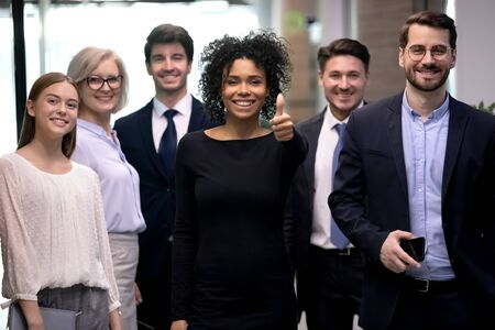 Smiling older and younger coworkers standing near happy african american colleague showing thumbs up gesture, looking at camera. Portrait of excited biracial woman satisfied with company team choice.