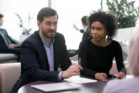 Focused mixed race female assistant watching young confident businessman in suit discussing contract terms with clients, holding business negotiations with partners in modern open space office.