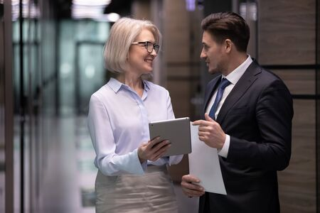 Smiling mature blonde female boss in glasses showing project details to younger male colleagues, standing together in office hall. Happy different ages workers discussing working issues in corridor. Stock Photo