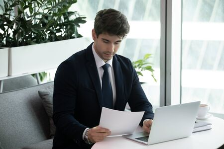 Young skilled thoughtful focused businessman supervisor boss manager entrepreneur reading paper project report, analyzing financial documentation, working on computer alone in modern workplace. Stock fotó