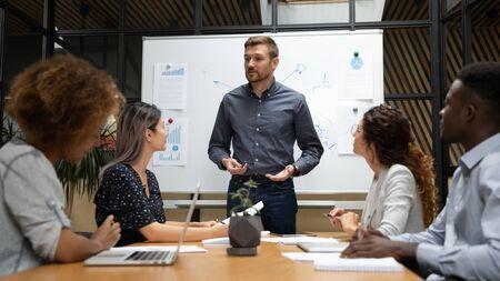 Selbstbewusster Geschäftsmannstand hält Team-Geschäftstreffen im Sitzungssaal Gespräch mit multiethnischen Mitarbeitern, kaukasischen männlichen Moderatoren oder Trainer sprechen, machen Präsentations-Brainstorming mit Geschäftsleuten beim Treffen Standard-Bild