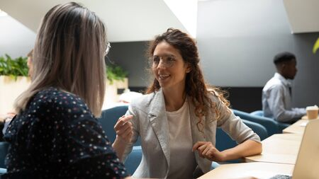 Smiling millennial women employee sit at office coworking desk talking sharing thoughts at break, young female workers speak chat discuss ideas in shared workplace, cooperating together at work
